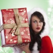 Santa claus lady wondering whats in gift box - Stock Photo