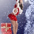 Santa claus brunette kissing a snowman — Stock Photo