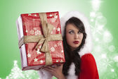 Santa claus lady wondering whats in gift box — Stock Photo