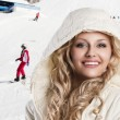 Girl with white hood, she's cold, foreground beautiful smile - Foto Stock