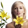 Beautyful blond girl with lily - Stock Photo
