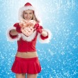 Santa claus girl showing gift box — Stock Photo
