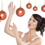 Preety girl playing joyfully between the christmas ball — Stock Photo #7531121