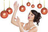 Preety girl playing joyfully between the christmas ball — Stock Photo