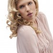 Blond young girl with curly hair looking towards camera with att — Stock Photo