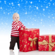 Christmas baby boy with gift box, he is standing and looks in to — Stock Photo #7631560