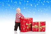 Christmas baby boy with gift box, he is standing and looks in to — Stock Photo
