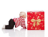 Christmas baby boy with gift box, baby on all fours — Stock Photo