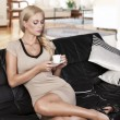 Sitting on sofa drinking from a cup. she's looking the cup. — Foto de Stock