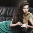 Young elegant girl in green with cup, she looks  in to the lens - Stockfoto