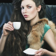 Young elegant girl in green with cup, she is bringigng the cup t — Stock Photo