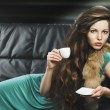 Young elegant girl in green with cup, she is lying on the sofa — Stock Photo #7850907