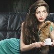Young elegant girl in green with cup, she is in front of the len — Stock Photo