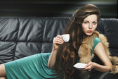 Young elegant girl in green with cup, she is lying on the sofa — Stock Photo