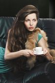 Young elegant girl in green with cup. she is looks at the left — Stock Photo