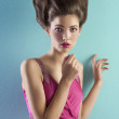 Young pretty model dressed in pink and with haute couture hair s — Stock Photo