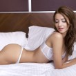 Beautiful brunette in bed — Stock Photo