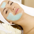 Young woman getting beauty skin mask treatment on her face with — Stock Photo #7359814