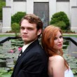 Stock Photo: Bride, groom sitting by lily pond