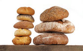 Bread loaf and buns on a shelf — Stock Photo