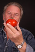Middle aged man showing tomato — Stock Photo