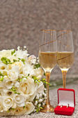 Wedding bouquet, rings and champagne — Stock Photo
