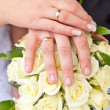 Foto de Stock  : Hands with wedding rings on wedding bouquet