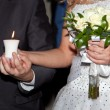 Burning candle in hands of the groom and the bride — Stock Photo #7137174