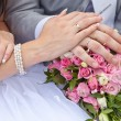 Hands of the groom and the bride on a wedding bouquet — Stock Photo