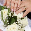 Stock Photo: Hands with wedding rings on bouquet