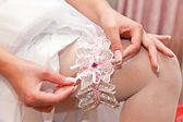 White garter on a foot of the bride — Stock Photo