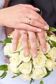 руки с обручальные кольца на свадебный букет — Стоковое фото