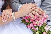 Mãos do noivo e da noiva em um buquê de casamento — Foto Stock