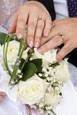 Mains avec anneaux de mariage sur un bouquet — Photo