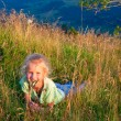 Girl and butterfly on mountain grasses — Stock Photo