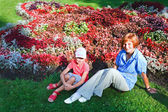 Mother with doughter near flowerbed — Stock Photo
