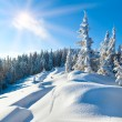 Snowdrifts on winter snow covered mountainside and sun - Stock Photo
