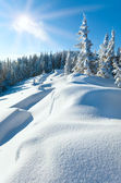 Snowdrifts on winter snow covered mountainside and sun — Stock Photo