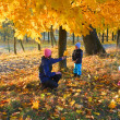 Family in autumn maple park — ストック写真