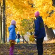 Family in autumn maple park — Zdjęcie stockowe #7463737