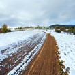 First winter snow on autumn mountain dirty road — Stock Photo