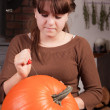 Young girl carving a pumpkin — Stock Photo