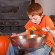 Stock Photo: Young boy eating pumpkins