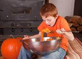Young boy eating pumpkins — Stock Photo