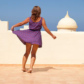 Age doesn't matter - tanned, fit middle-aged woman dances on the — Stock Photo