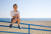 Young boy sitting on a metal railing, beach and sea in the backg — Stock Photo