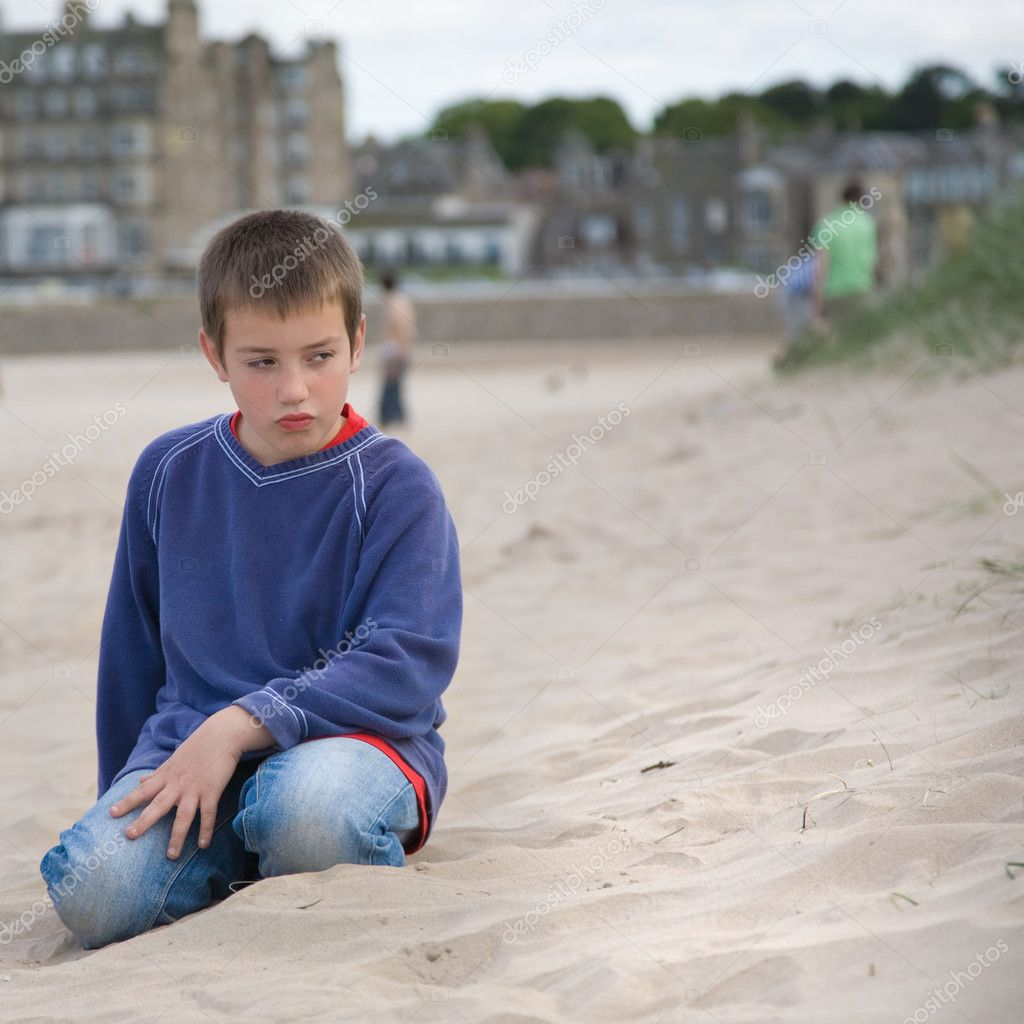 I am bored (little boy making a bored face on a beach, overcast  Stock Photo #7379061