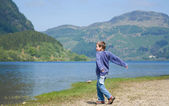 Little boy is throwing stones in the water, Loch Lubnaig — Stock Photo