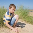 Cute little boy playing with sand in dunes next to the sea — Stock Photo #7542680