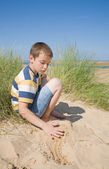 Cute little boy playing with sand in dunes next to the sea — Stock Photo